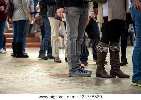 Crowd of unrecognizable people wait in line in a urban setting, outdoors. People standing in a queue.