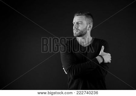 Guy with beard on unshaven face pose with folded hands on dark background. Barbershop, male beauty, fashion, style concept, black and white, copy space