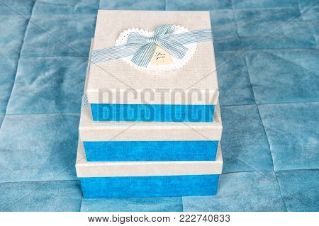 Boxes with heart and ribbon bow on blue bed cover background. Boxing day concept. Valentines day, birthday, anniversary, holidays celebration.