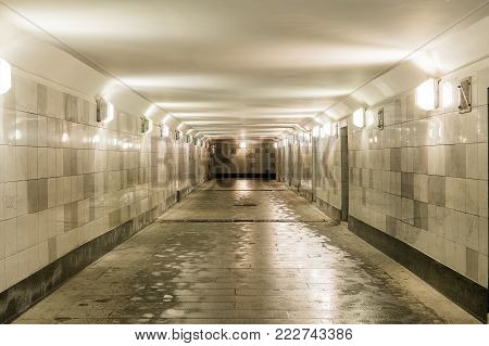 The underground passage is faced with gray granite and marble. People cross the road through the tunnel. The ladder is up. City center.