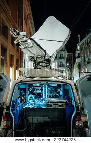Opened door of parked satellite TV van transmitting breaking news events to satellites for broadcast around the world at night in city