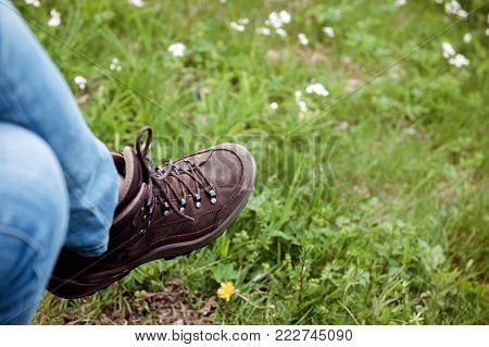 Horisontal image of crossed female legs wearing Alpine Touring Randonee Boots on woman feet in green mountain field.