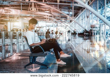 Pensive young Brazilian tourist female is sitting inside of modern waiting hall of airport terminal and waiting for her flight; cute black girl is waiting indoors of contemporary railway station depot