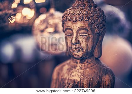 Vintage style photo of the wooden statue of Buddha, God of oriental religion, conceptual picture of meditation, mindfulness and inner peace