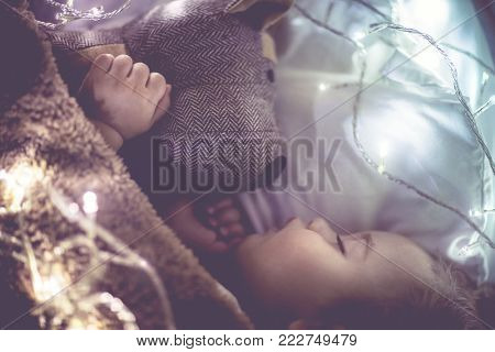 Cute little baby sleeping at home in his bed with his best friend, soft toy dog, vintage style photo with glowing lights, happy toddler dreaming