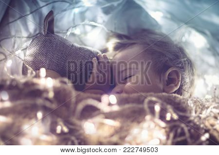 Sweet little baby sleeping with soft toy in the bed at home, smiling in a dream, magic fantasy night, vintage style photo