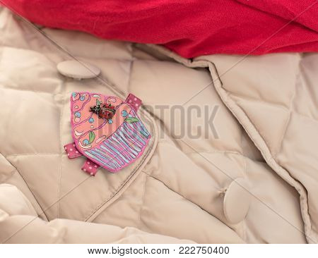 Beige jacket, red, scarf, pink brooch. A fashionable look for women