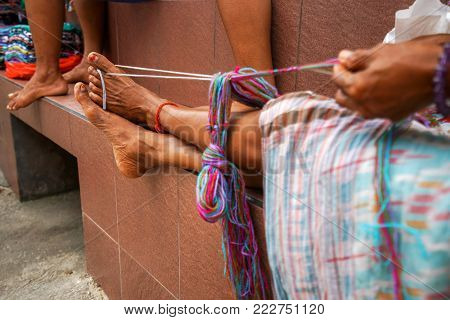 tanned legs of an old authentic Indonesian woman at work. The legs of an ordinary Asian woman hold the thread for knitting.