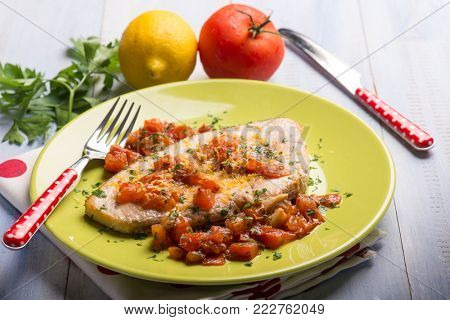 swordfish with fresh tomatoes and grated lemon peel, selective focus