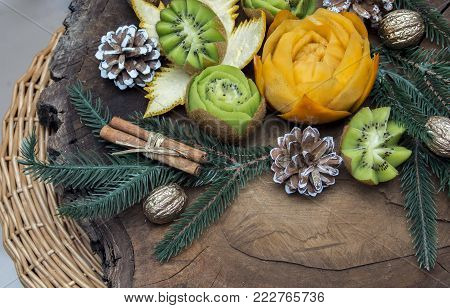 Composition Of Fresh Carved Fruits Decorated With Fir Branches