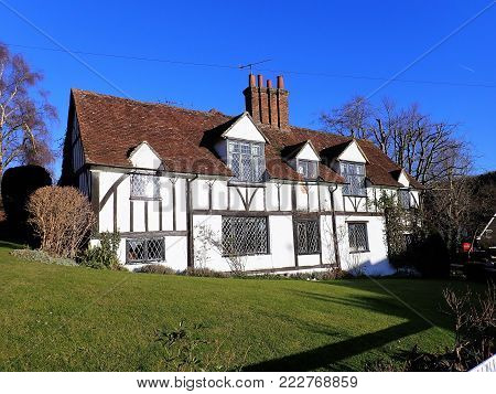 Whitewashed timbered medieval cottage in a rural English village