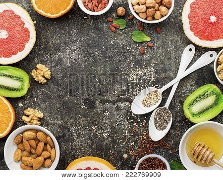 Ingredients of healthy dietary food breakfast pink grapefruit, orange, chia seeds, quinoa, green herbs, kiwi, wild rice, almonds, walnuts, hazelnuts on a gray background. The concept of natural organic food. Top View