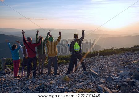 Happy friends, travelers, with open arms, stands on the top in the mountains, admiring sunset and enjoys life. Happy people in nature. Back view, back light.