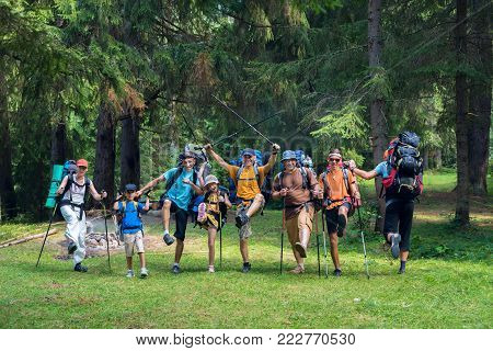 Company of joyful friends, travelers with backpacks stands on a clearing, among the coniferous forest and has fun. Happy people in nature.