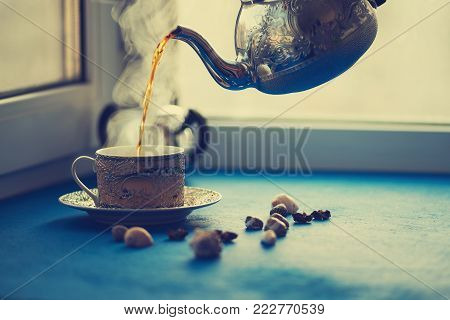 Hot tea is poured from a vintage steel kettle into a cup with an ornament against the blurred background.