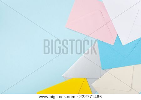 Border from colorful envelopes on blue table top view. Mockup for business mail, blogging and office correspondence. Flat lay.