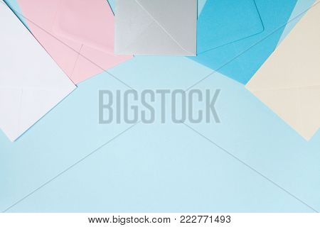 Colorful envelopes on blue table top view. Mockup for business mail, blogging and office correspondence. Flat lay style.