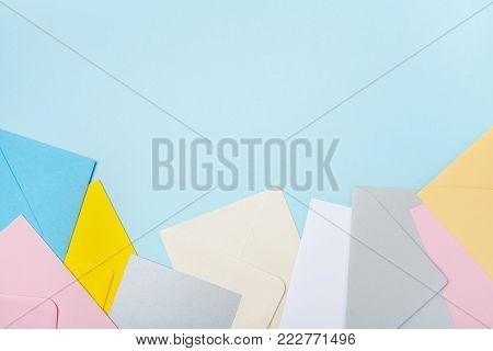 Heap of colorful envelopes on blue working desk top view. Mockup for business mail, blogging and office correspondence. Flat lay.