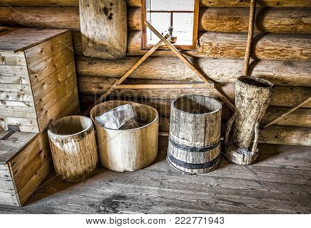 Old wooden house utensils in the corner of a log-built rural house.
