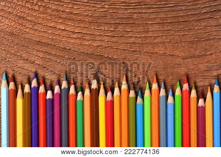 Color pencils on a brown background. Many different colored pencils. Colored drawing pencils in a variety of colors
