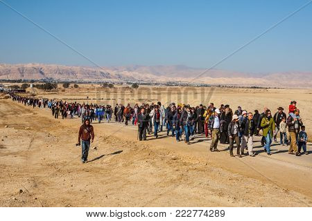 THE BORDER WITH JORDAN, ISRAEL - JANUARY 18, 2008: Pilgrims and tourists walk through the desert after visiting the site of the Baptism of Jesus in the Jordan River