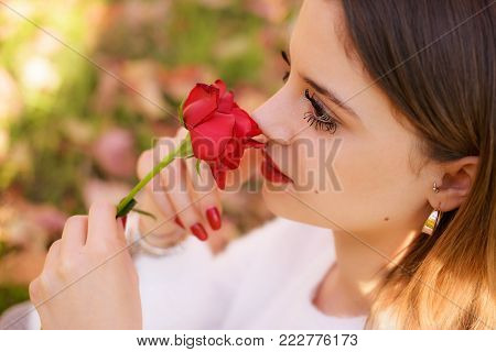 Girl sniffing a red rose in San Valentine day