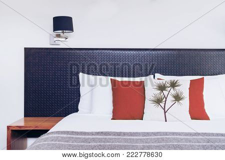 Bed headboard design in bedroom interior with pillows and blanket on the bed. Close up view of Australian-style bedroom with cozy interior design for hotel, home and resort accommodation business.