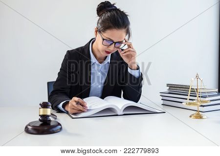 Legal law, advice and justice concept, Professional Female lawyers working on courtroom sitting at the table and signing papers with gavel and Scales of justice.