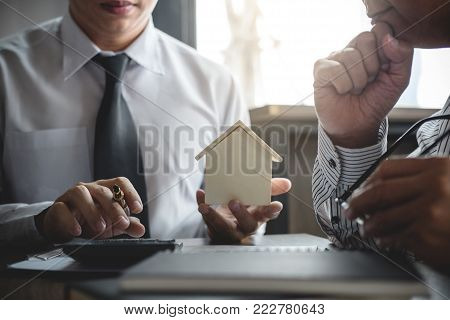 Real estate broker agent being analysis and making the decision a home estate loan to customer, Agent man is using calculator to presentation detail and waiting for his reply to finish.
