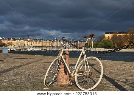 Bicycle infront of a view at the old European city at sunset. Bicycle parked near water in Stockholm, Sweden.