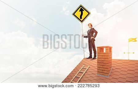 Young determined businessman standing on house roof and showing yellow roadsign. Mixed media