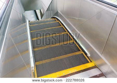 Escalator in metro. Moving up staircase. escalator. electric escalator.Close up to escalators. electric escalator.Close up floor platform. yellow bands. metal line steel. yellow gray steel line.Moving
