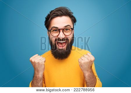 Excited bearded man in glasses standing with fists up on blue background.