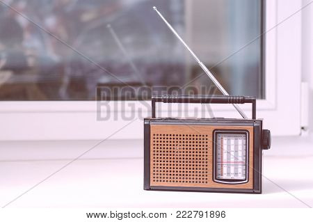 Old Brown Retro Radio Is On The White Window Sill Of The Room From The Directional Antenna.