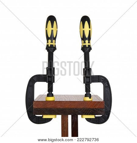 clamps of yellow color hold two wooden bars on a white background. Use F-clamp to holding or catch wood in woodworking.