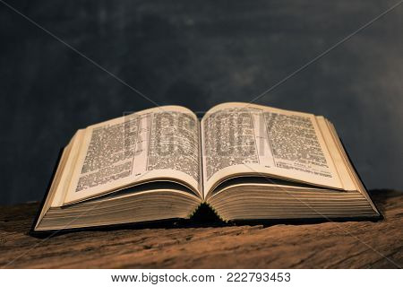 Open Holy Bible on a old oak wooden table. Beautiful dark background.Religion concept