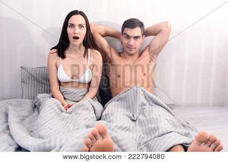 Confident man lying on the bed with his hands behind his head, the woman shocked at the size of his penis, and humor. the concept of a healthy sexual relationship.