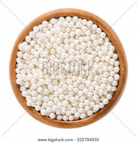 White nonpareils in wooden bowl. Hundreds and thousands. Decorative confectionery of tiny balls, made with sugar and starch, used for decoration. Macro food photo close up from above over white.