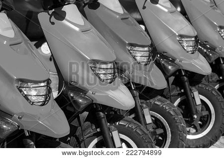 red scooters or motorcycles for sale or hire standing in row with wheels and lights sunny day outdoor, hiring transportation, traveling