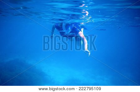 Woman swimming underwater in full-face mask. Blue sea banner template with text place. Underwater photo of female snorkel in modern gear. Snorkeling in coral reef with coral fish. Seaside vacation