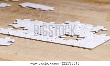 white jigsaw/puzzle to be completed , over wooden table background, symbol of problem solving