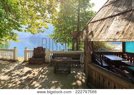 Old wooden summerhouse with benches on the shore of Lake Ritsa, Abkhazia