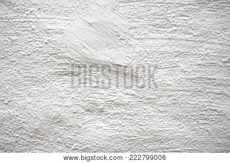 Painted wall with subtle texture closeup photo. White plaster with brushed texture. White house wall. Greek architecture background. Pottery house wall. White painted surface. Vintage or shabby chic