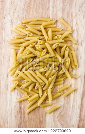 Raw macaroni of hard varieties on a wooden table. A pile of macaroni penne scattered on a close-up table.
