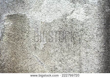 Stained wall with rough texture closeup photo. Vintage or shabby chic background. Stained wall with distressed marks. Aged concrete wall with cracks and noise. Grungy photo background. Grey concrete
