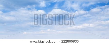 Wide blue sky background, natural panorama with white cumulus clouds over horizon poster