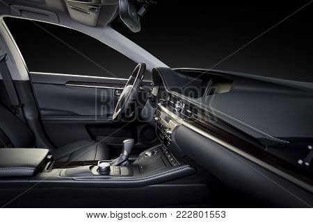 Luxury car inside. Interior of prestige modern car. Comfortable leather seats. Black perforated leather cockpit with isolated black background, clipping path included