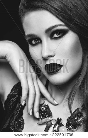 beautiful young woman with dark lips and smokey eye makeup. Long red hair. Studio beauty shot. Copy space.