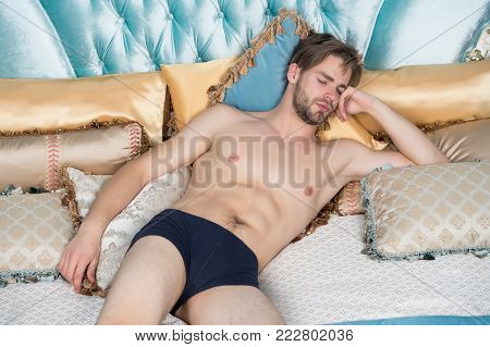 Dream, slumber concept. Man sleep in blue bed. Macho with sexy body in briefs in bedroom. Fashion, male underwear.