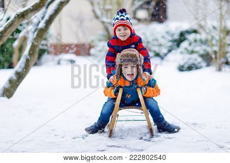 Two kid boys having fun sleigh ride during snowfall. Children sledding on snow. siblings riding a sledge. Twins play outdoors. Friends sled in snowy winter park. Active fun for family vacation.
